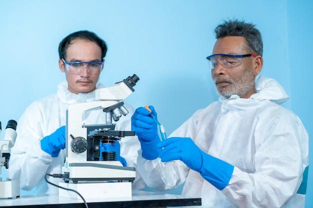 Close-up da equipe os médicos em roupas de proteção de materiais perigosos epi usam luvas de borracha médica usam microscópio no laboratório, cientistas trabalhando no laboratório.