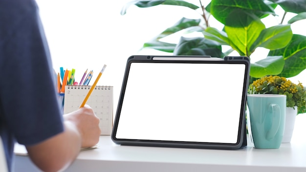 Close-up da escrita da mão do homem e tablet digital com fundo de mesa de trabalho de tela em branco para mock up, modelo