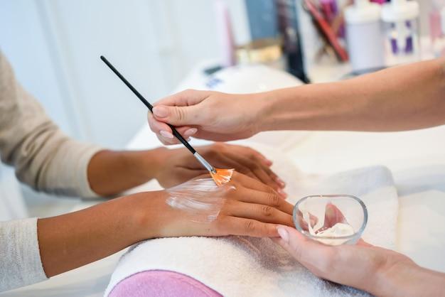 Close-up da esteticista aplicar creme na mão da mulher, usando o pincel.