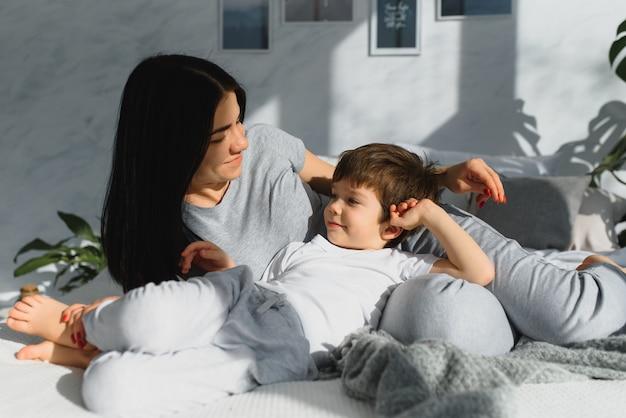 Close-up da família feliz jogando sobre a cama em uma manhã relaxada.