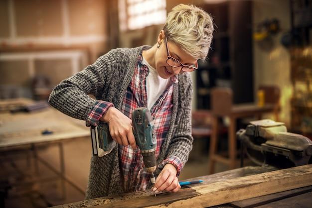 Close-up da fêmea trabalhadora alegre cabelo curto, trabalhando com uma furadeira elétrica em uma oficina de tecidos