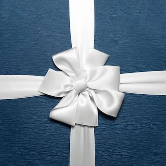 Close-up da fita de embrulho branca em forma de laço na caixa de presente azul.