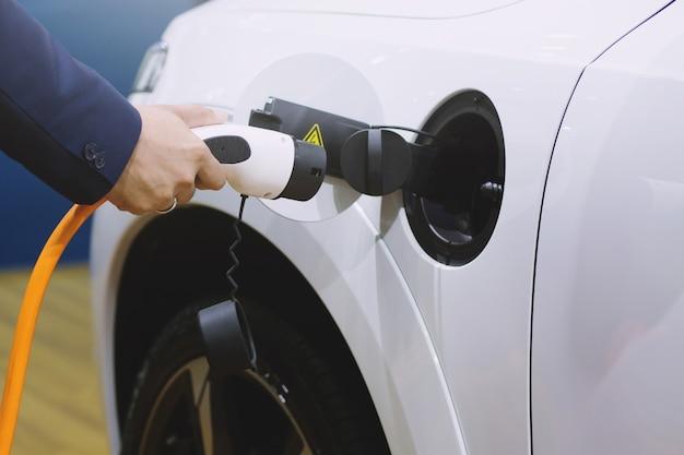 Close-up da fonte de alimentação conectada a um carro elétrico sendo carregado.