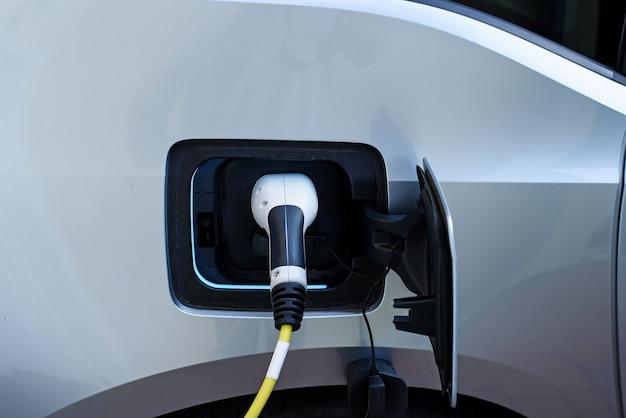 Close-up da fonte de alimentação ligada a um carro elétrico moderno sendo carregado