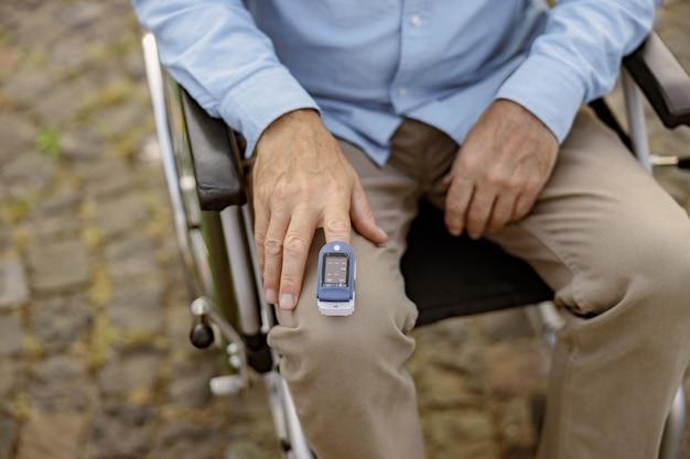 Close-up da foto da mão de um homem com deficiência em cadeira de rodas usando o oxímetro de pulso na ponta do dedo para medir