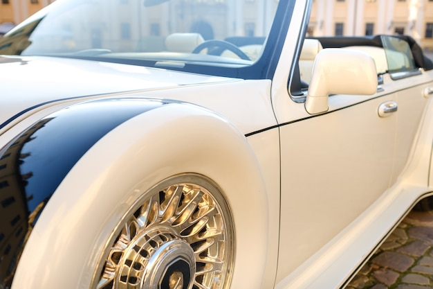 Close-up da frente de um carro vintage branco no pátio do castelo.