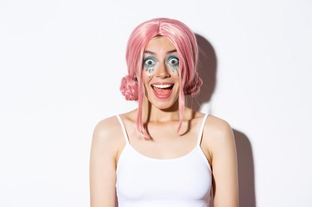 Close-up da garota feliz surpresa na peruca rosa, sorrindo e olhando animado para a câmera, em pé, comemorando o dia das bruxas.