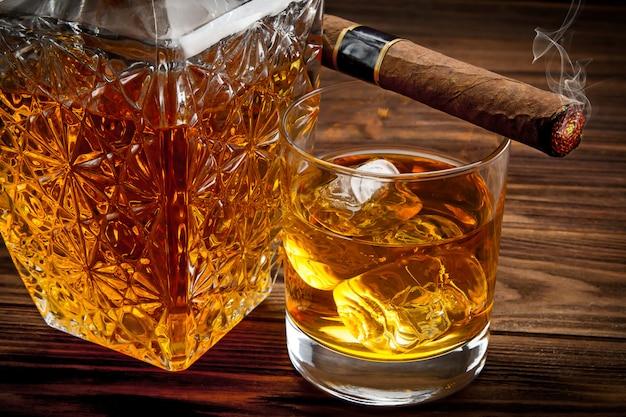 Close up da garrafa, copo com uísque e fumar charuto