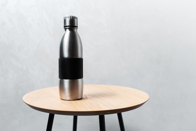 Close-up da garrafa de água térmica reutilizável de aço na mesa de madeira.