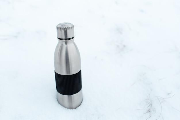 Close up da garrafa de água térmica reutilizável de aço na neve. fundo de inverno com espaço de cópia.