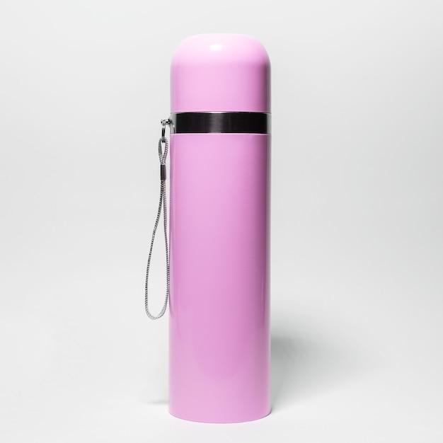 Close-up da garrafa térmica de aço inoxidável rosa isolada no branco.