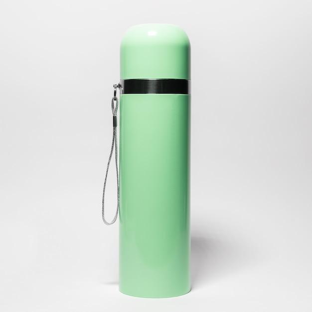 Close-up da garrafa térmica de aço inoxidável verde isolada no branco.