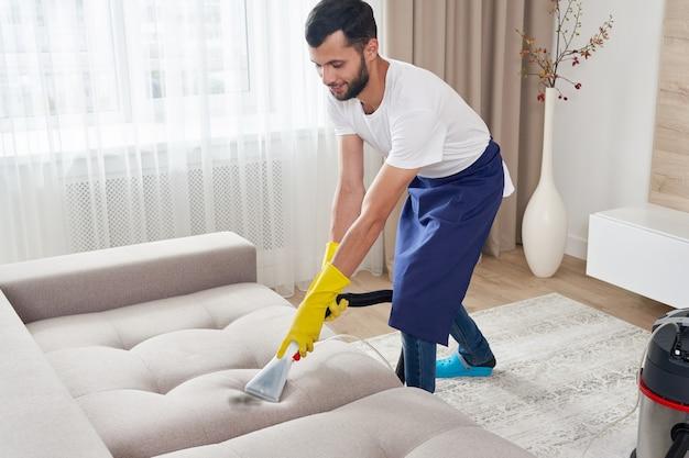Close-up da governanta segurando um aspirador de pó moderno e limpando o sofá sujo com detergente profissional. conceito de limpeza profissional em casa