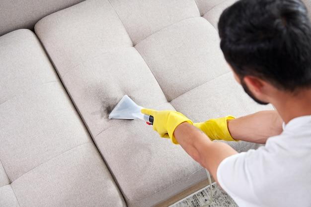 Close-up da governanta segurando um aspirador de pó moderno e limpando o sofá sujo com detergente profissional.