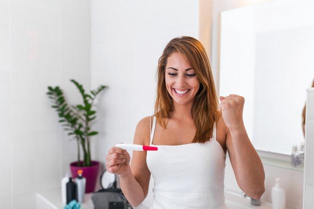 Close-up da jovem fêmea vestida de blusa branca, olhando para o resultado do teste de gravidez com sorriso positivo