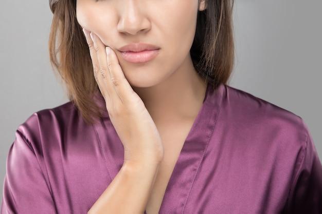 Close up da jovem mulher bonita que sofre da dor de dente, saúde e cuidado dentais.