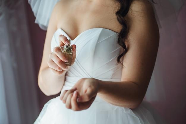 Close up da jovem noiva se preparando com perfumes em casa de manhã no dia do casamento