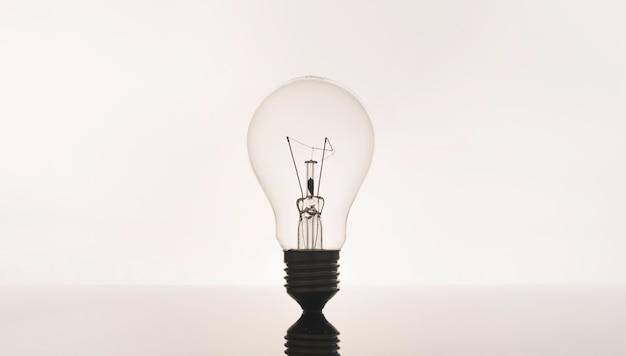 Close-up da lâmpada no fundo branco, a ideia criativa e o conceito de inovação.