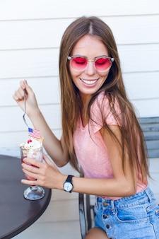 Close-up da linda garota sentada em uma cadeira tomando sorvete com cereja no topo com uma colher. ela usa shorts jeans, blusa rosa e sorrisos. ela tem óculos rosa