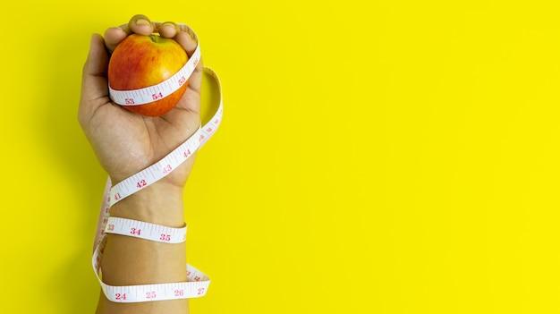 Close-up da maçã vermelha na mão esquerda enrolado em uma fita métrica, saúde e conceito de dieta
