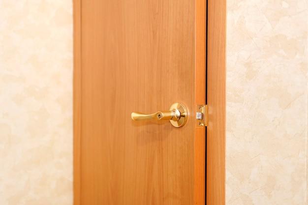 Close-up da maçaneta da porta. porta do quarto de hotel ou apartamento com porta aberta