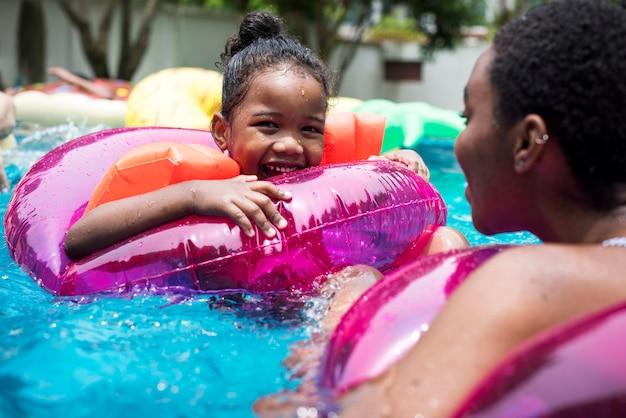 Close up da mãe e da filha pretas que apreciam a associação com tubos infláveis