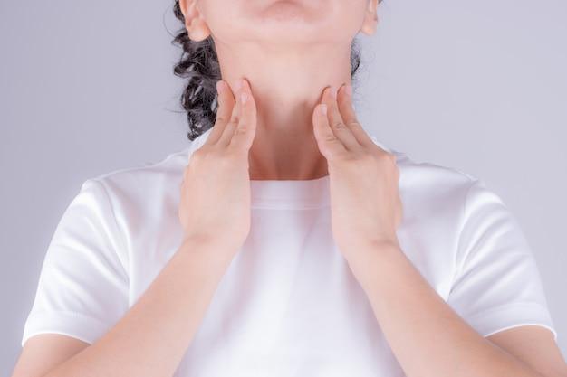 Close up da mão bonita da jovem mulher que toca em seu pescoço doente.