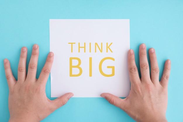 Close-up da mão colocando o grande texto pensar em papel branco sobre o fundo azul