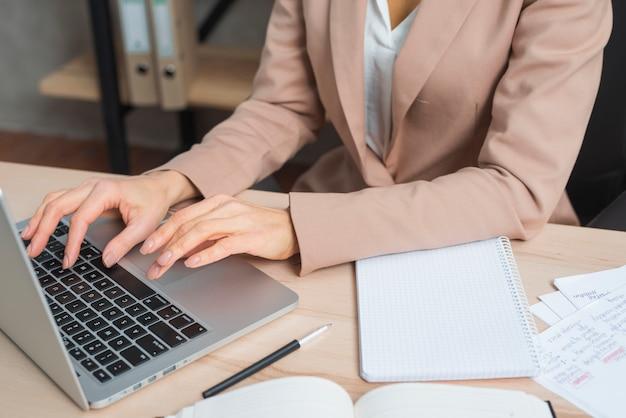 Close-up da mão da empresária digitando no laptop com caneta; bloco de notas diário e espiral na mesa de madeira