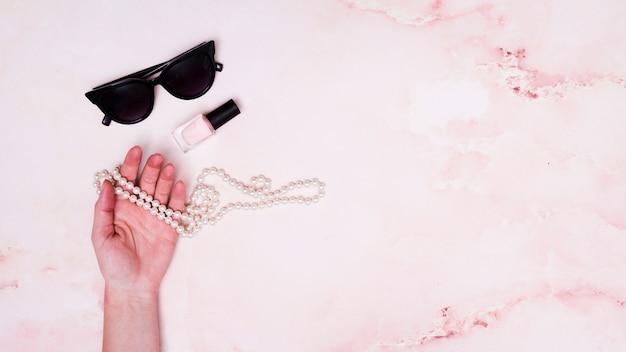 Close-up da mão da fêmea segurando o colar de pérolas; garrafa de verniz de unhas e óculos escuros em fundo rosa