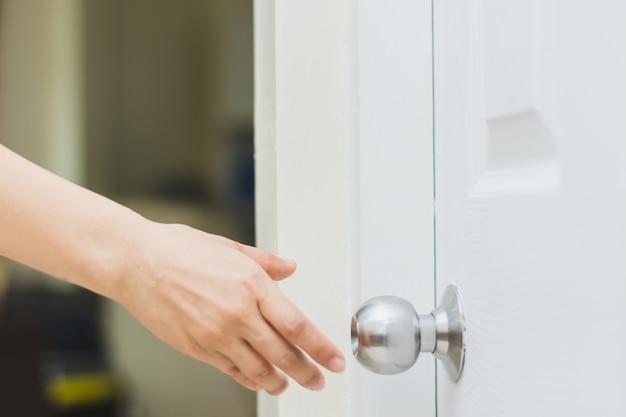 Close-up da mão da mulher, atingindo a maçaneta da porta, abrindo a porta