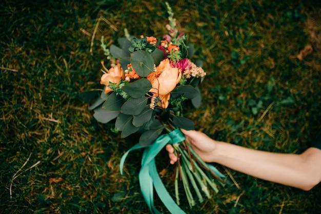 Close-up da mão da mulher e buquê de flores, deitado no chão.
