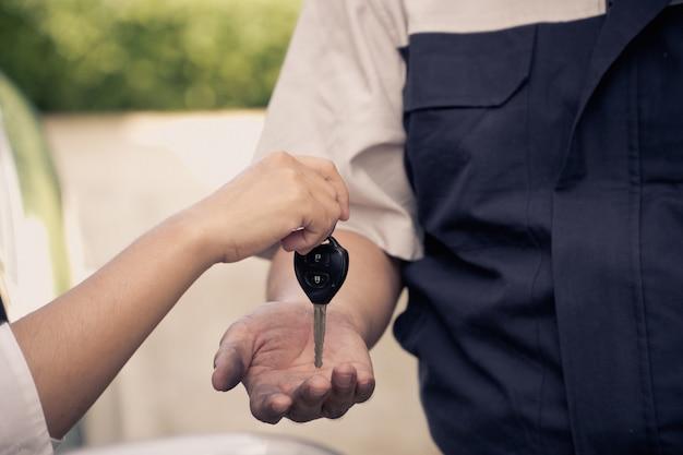 Close-up da mão da mulher está enviando as chaves do carro para o mecânico de automóveis.