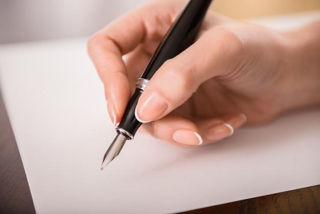 Close-up da mão da mulher está escrevendo no papel.