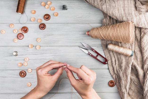 Close-up da mão da mulher, inserindo a linha na agulha com o botão; cortador; pano no pano de fundo de madeira