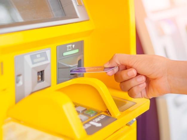 Close-up da mão da mulher, inserindo o cartão de débito em uma máquina de atm.