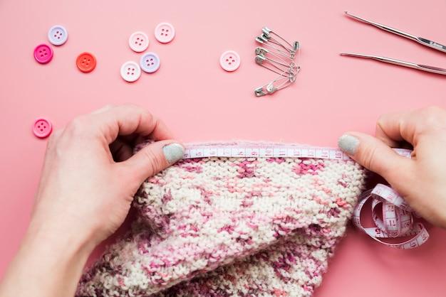 Close-up da mão da mulher, medindo o tecido de malha com botões; alfinetes de segurança e agulha de crochet