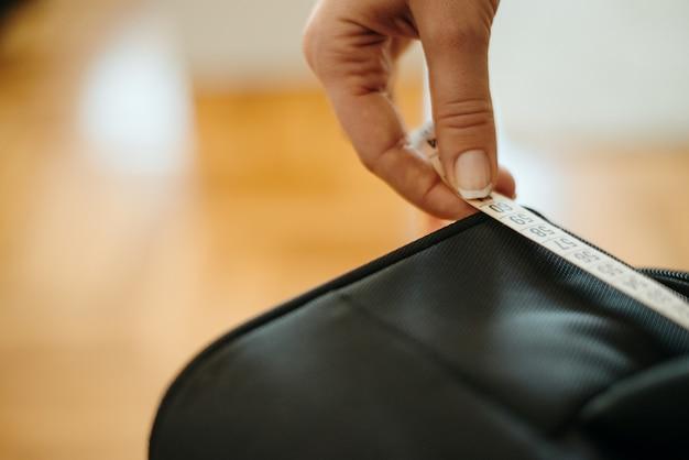 Close up da mão da mulher usando a fita de medição para medir a bagagem de mão.