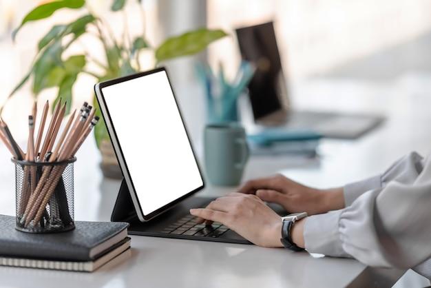 Close-up da mão da mulher usando a tela em branco do tablet digital no escritório