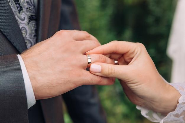 Close-up da mão da noiva coloca um anel de casamento no dedo dos noivos, a cerimônia na rua, foco seletivo