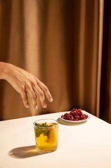 Close-up da mão da pessoa sobre o copo de coquetel caseiro perto de sementes de romã na mesa