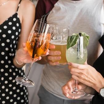 Close-up da mão de amigos segurando o copo de bebidas