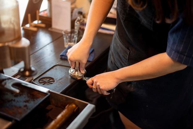 Close-up da mão de barista está preparando café na cafeteria