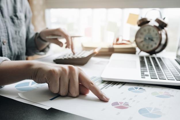 Close-up da mão de empresária ou contador segurando a caneta trabalhando na calculadora para calcular dados comerciais