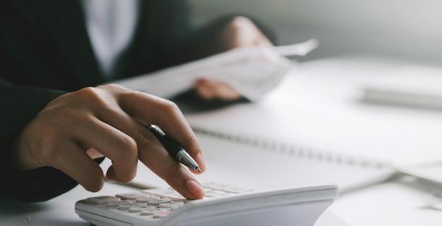 Close-up da mão de empresário ou contador segurando a caneta trabalhando na calculadora para calcular dados comerciais, conceito de contabilidade financeira