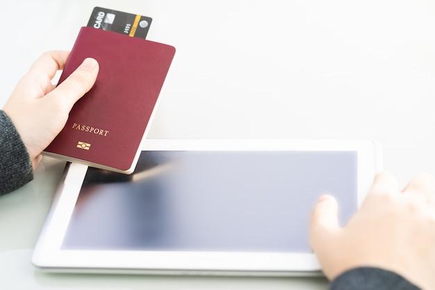 Close-up da mão de mulheres segurando o passaporte com tela de espaço em branco do computador tablet