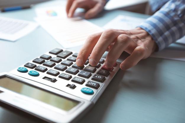 Close-up da mão de um contador em uma calculadora que faz um relatório financeiro.