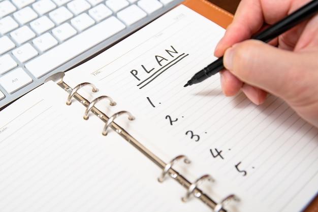 Close-up da mão de um empresário, escrevendo o plano e a lista no diário.
