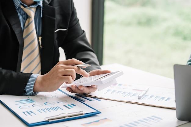 Close-up da mão de um empresário segurando uma calculadora com gráfico de documentos colocado na mesa do escritório.