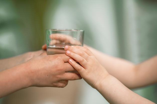 Close-up da mão de um homem dando um copo de água filtrada para uma criança